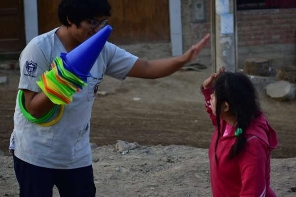 A volunteer from Warmakuna Hope giving a child a highfive