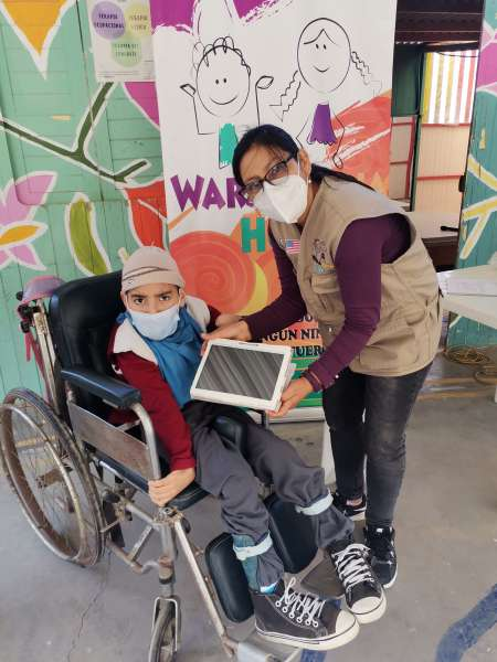 A Warmakuna Hope volunteer providing a child in a wheelchair a brand new ipad